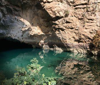 Glasklares Wasser im See der Altinbesik-Höhle mit Spiegelungen der Felsen.