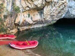 Rote Gummiboote im glasklaren Wasser im See der Altinbesik-Höhle mit Spiegelungen der Felsen.